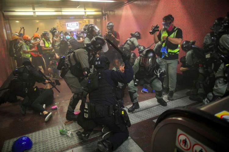 「反送中」警民衝突不斷,圖為港警衝進地鐵站施放催淚彈,逮捕示威者。(美聯社)