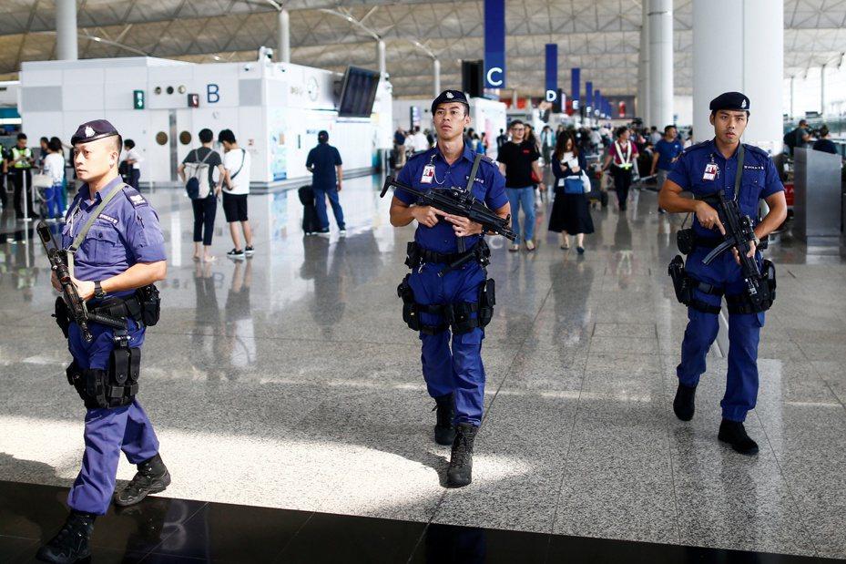 香港警察荷槍實彈在機場出境大廳巡邏。 (路透)
