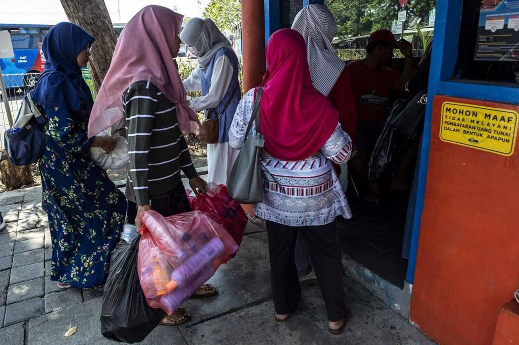 印尼泗水民眾用塑膠瓶換公車票。(法新社)