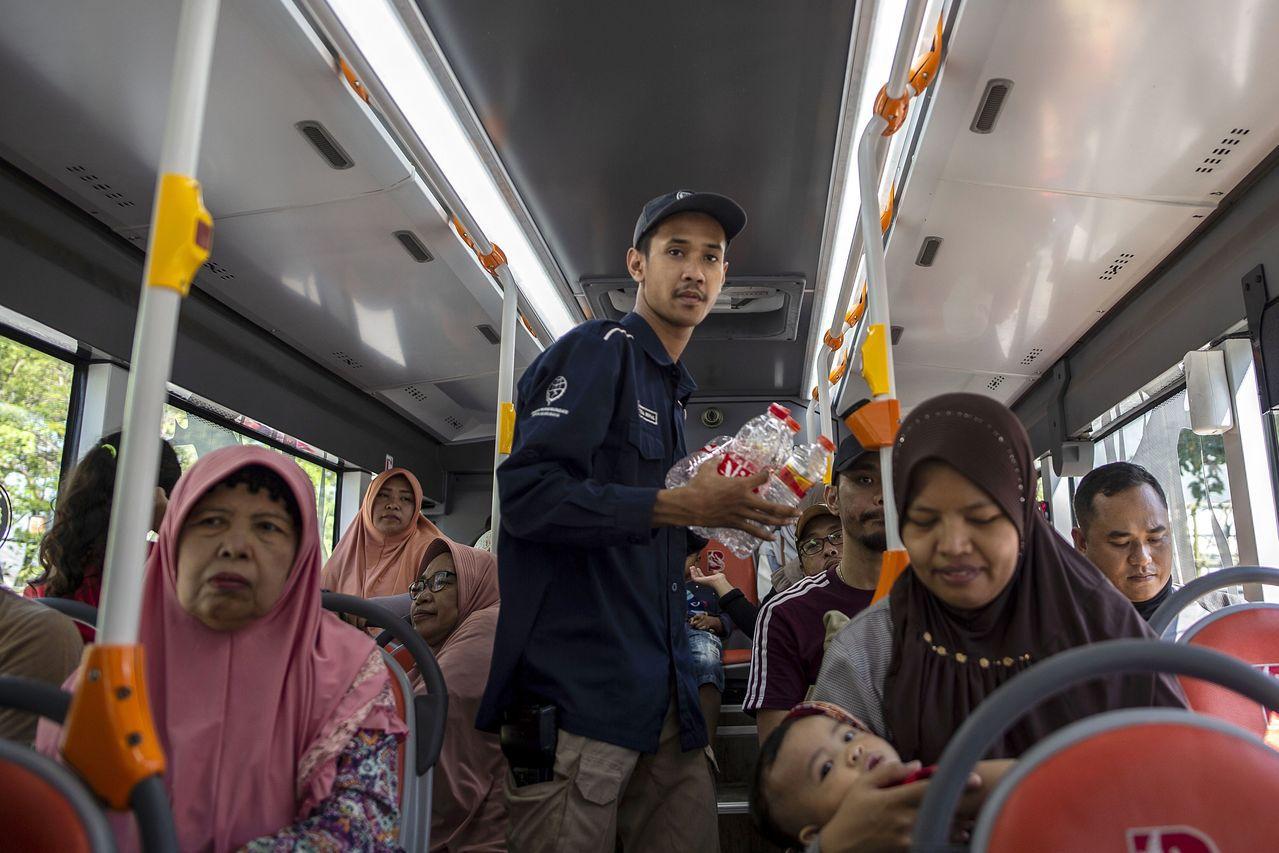 車掌在車上收集乘客用過的塑膠瓶。(法新社)
