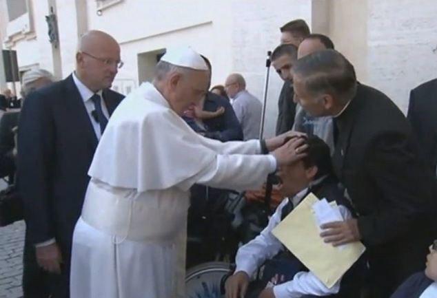2013年5月19日,教宗方濟各(前左)疑似在梵蒂岡聖伯多祿廣場為這名坐輪椅男子...
