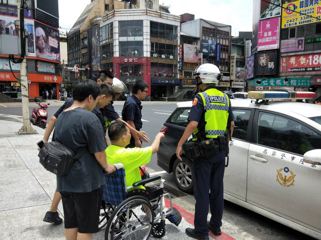 一名截肢坐輪椅男子今天中午被搶,警方趕至現場處理。記者游明煌/攝影