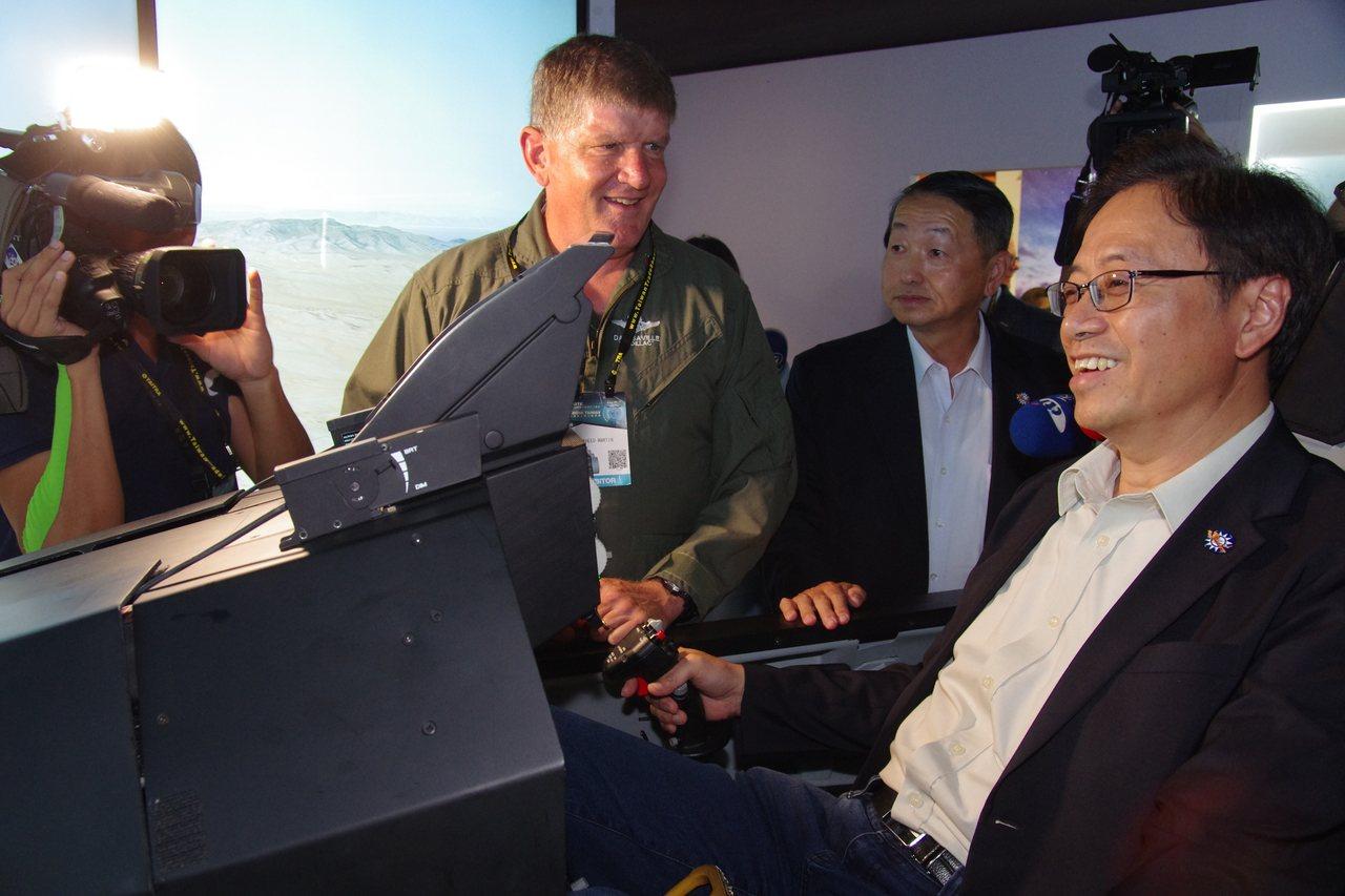 行政院前院長張善政坐進模擬機艙內,體驗駕駛戰鬥機的臨場感。攝影/記者程嘉文
