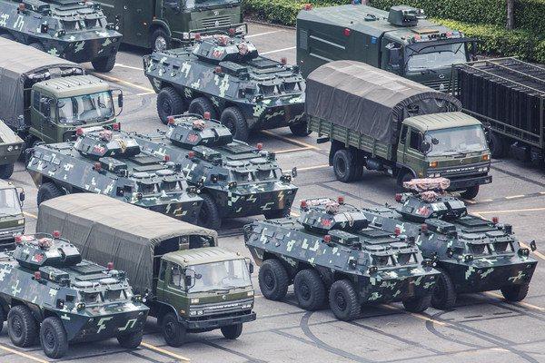 大量軍用卡車、裝甲車和水炮車等裝備整齊停放。圖/路透社