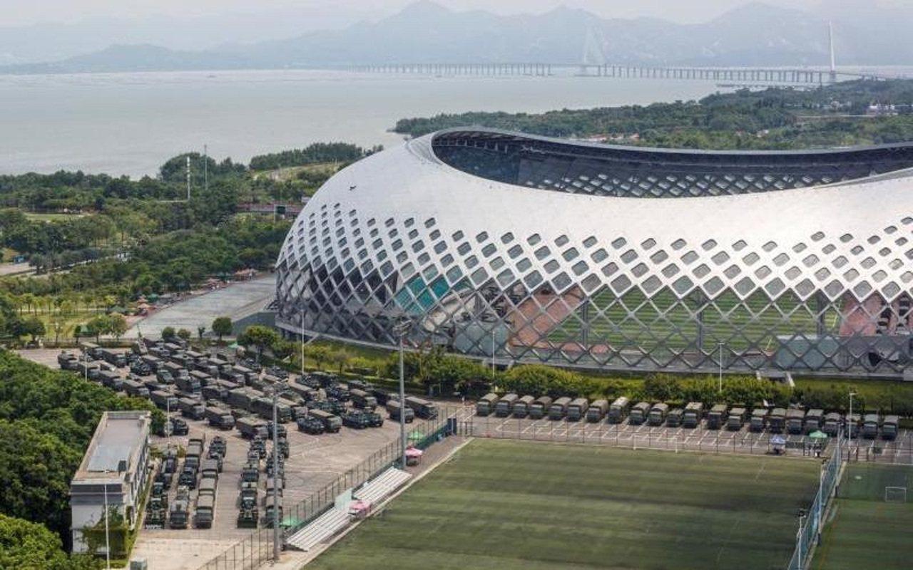距離香港大約7公里、與香港只有一灣之隔的深圳灣體育中心外,停了數十輛卡車和裝甲運...