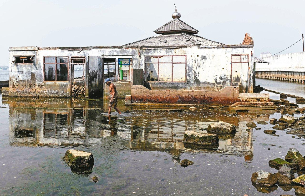 印尼首都雅加達正在下沉,一名男子行經北區一座沉沒在水中的廢棄清真寺。 (法新社)