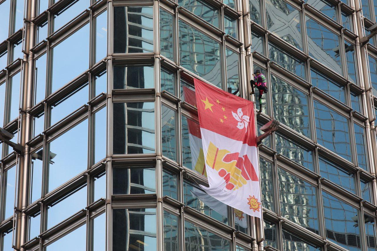 外號「法國蜘蛛人」的羅貝爾,16日爬上李嘉誠的長江集團中心大廈,掛上巨型布條,上...