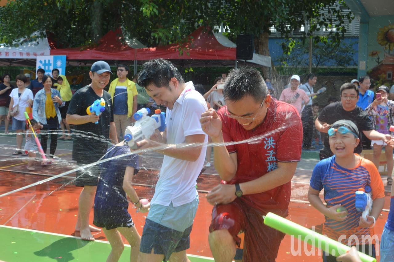 蔣萬安(左)、洪孟楷(右)到新北泰山玩水球,成眾人攻擊箭靶,渾身濕透。記者施鴻基...