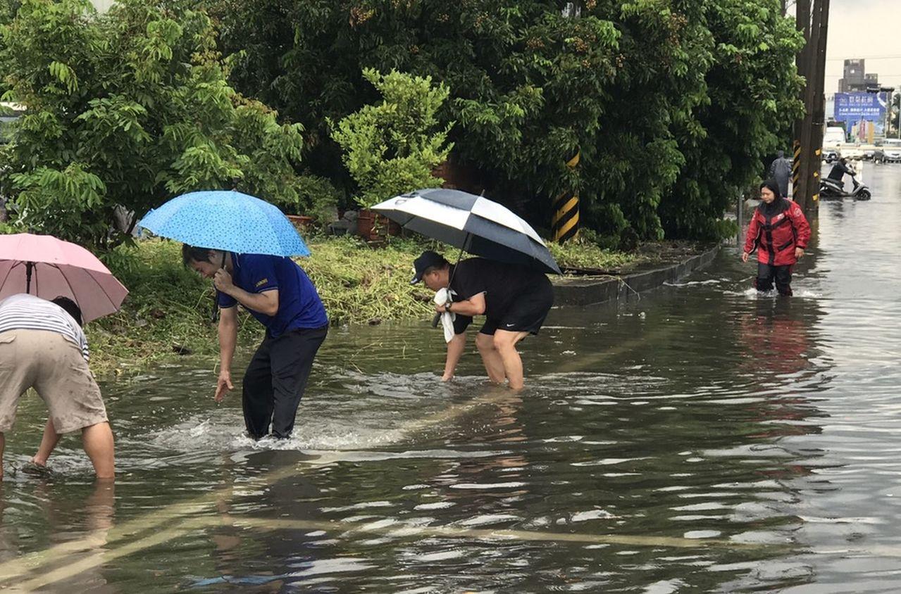 台中市警局烏日分局大肚派出所警員冒雨站在泥流傾瀉而下的積水處指揮交通,大肚派出所...
