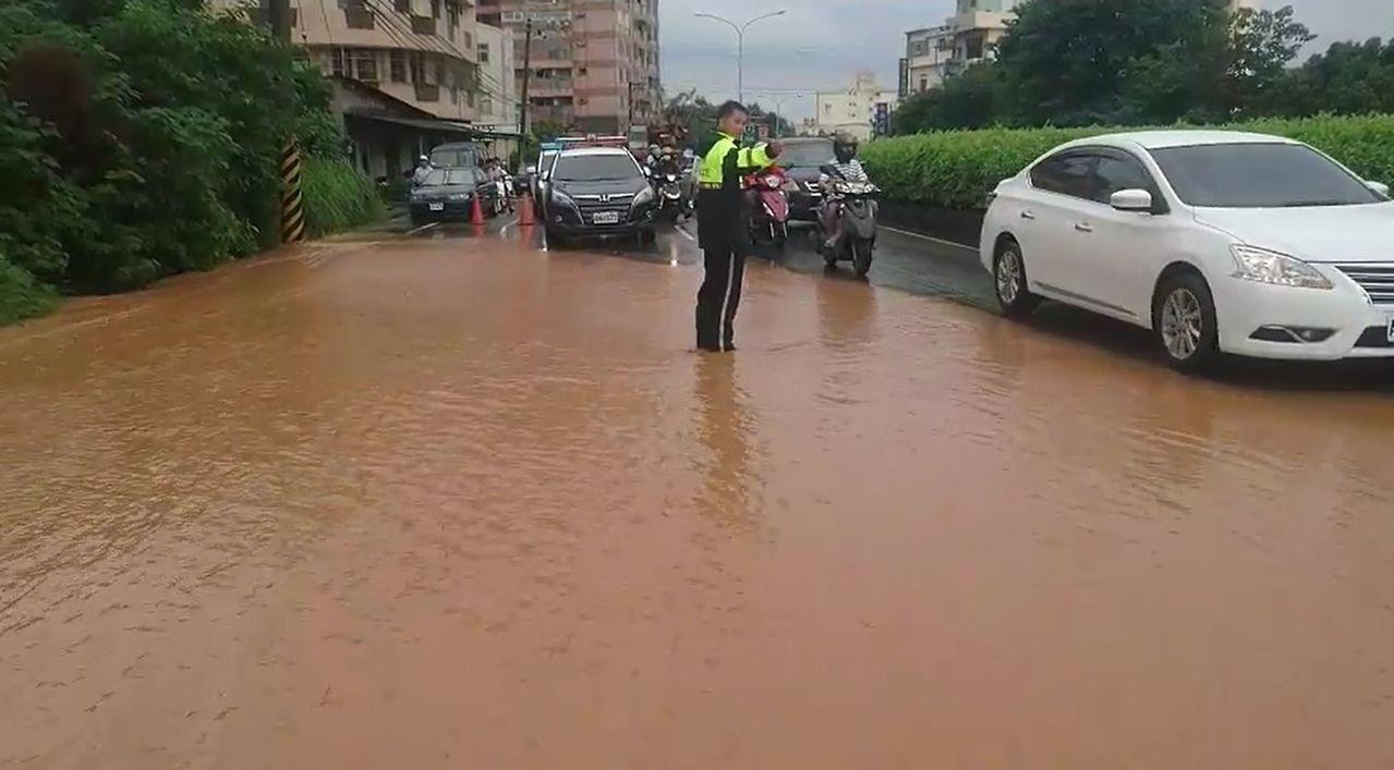 台中市警局烏日分局大肚派出所警員冒雨站在泥流傾瀉而下的積水中指揮交通,路過民眾看...