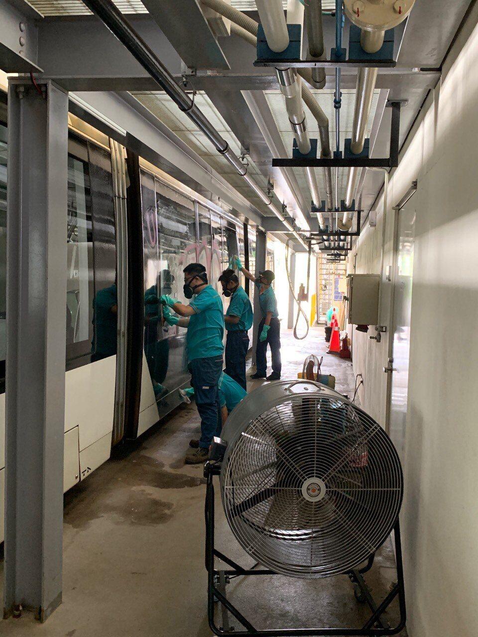 高雄捷運公司人員清除輕軌列車車廂上的塗鴉。圖/高雄捷運公司提供