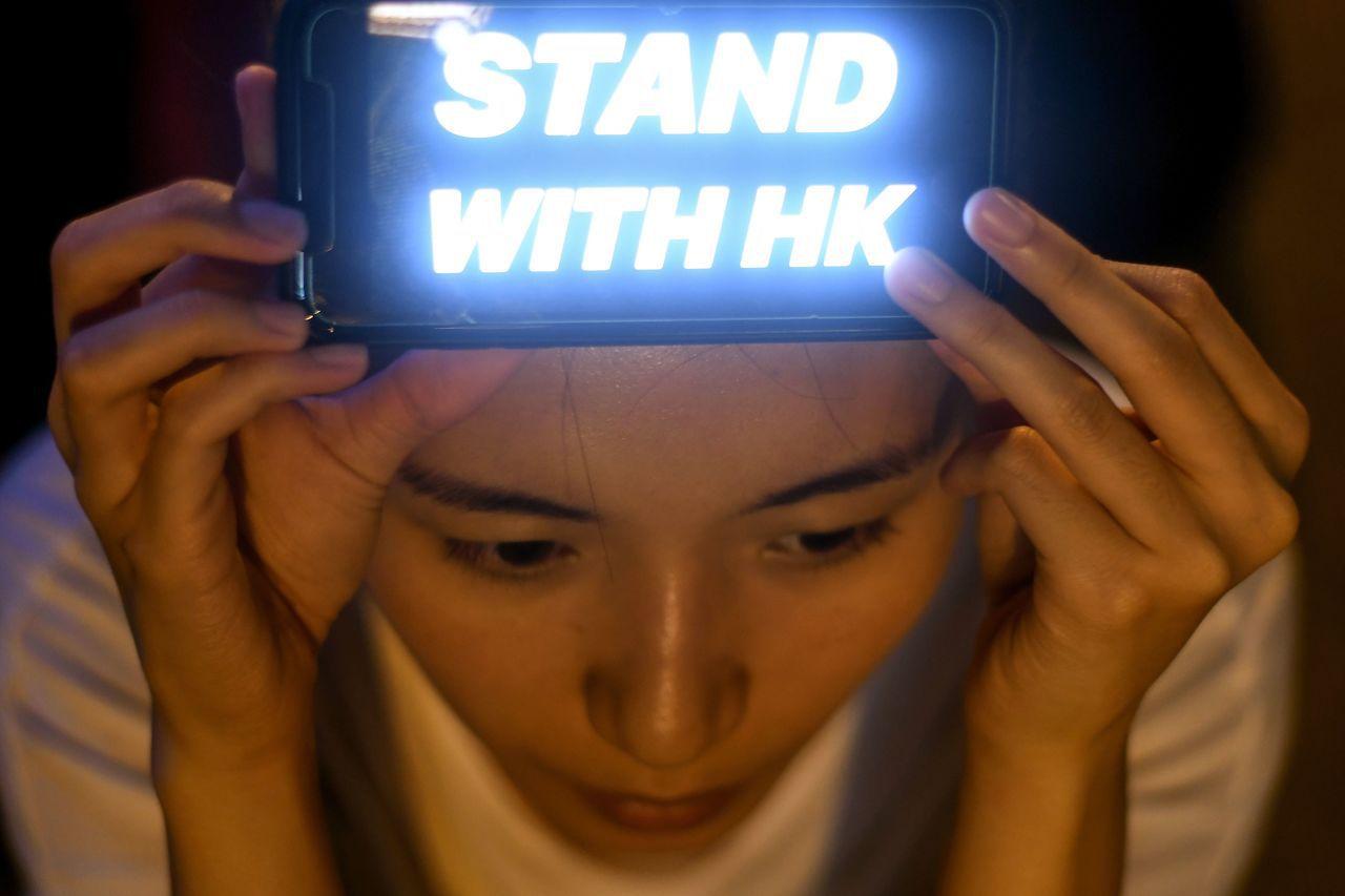 支持民主的香港市民在頭上舉起照明裝置,寫著「堅守香港」。 (Getty Ima...
