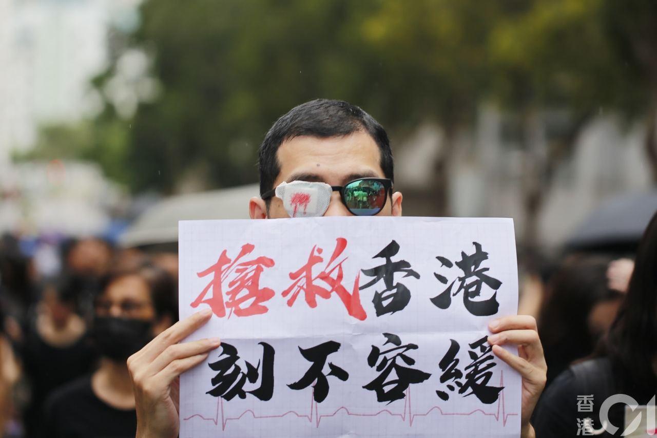 遊行民眾手持標語。 香港01記者梁鵬威攝