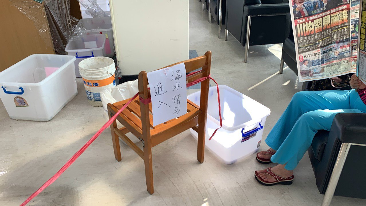 大墩文化中心期刊室漏水嚴重,民眾在水桶旁繼續閲報。圖/江肇國提供
