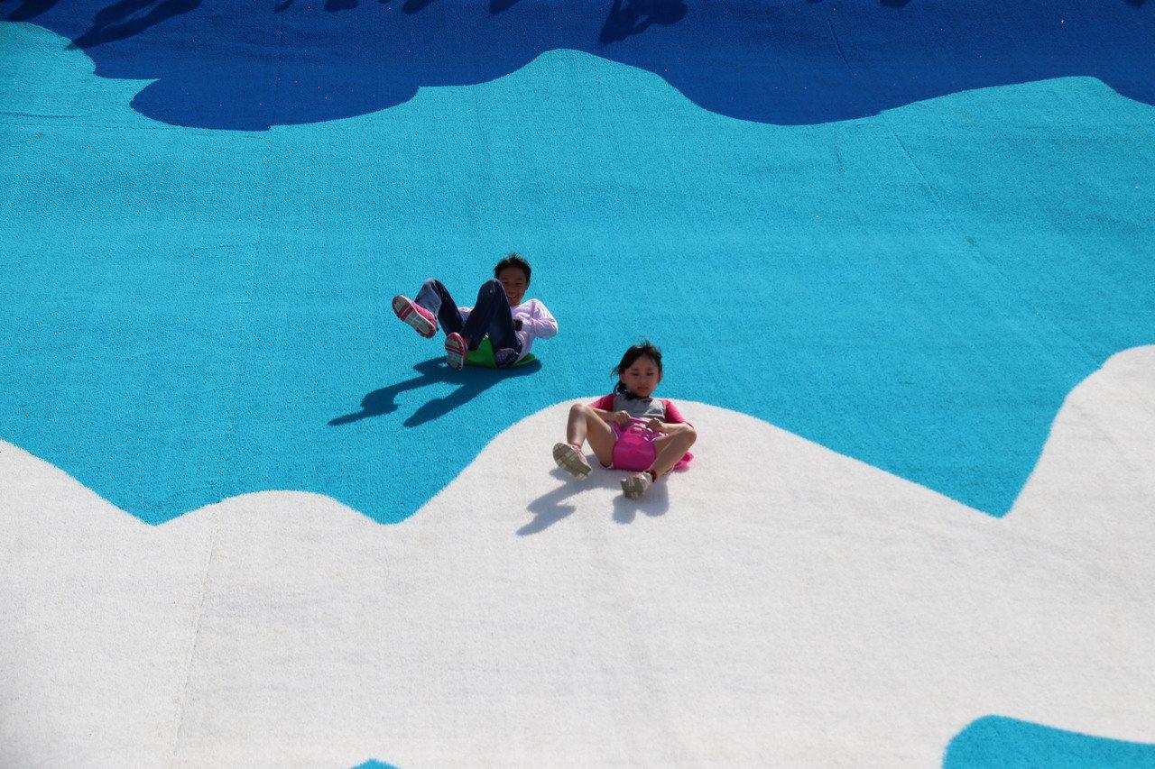 新北大都會公園「瀑布滑草場」今舉辦啟用活動,不少民眾一早就到現場享受滑草樂趣。記...