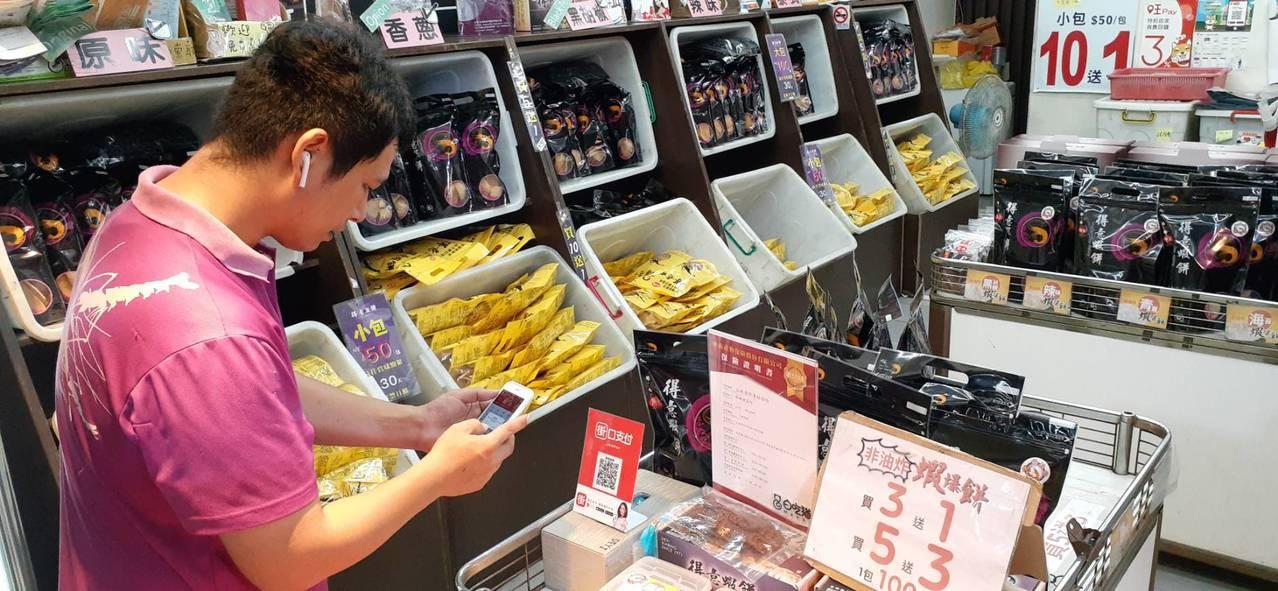 消費者前安平得意蝦餅店,可使用智慧手機買蝦餅。記者黃宣翰/翻攝
