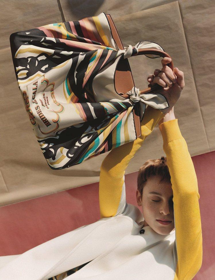 將絲巾外罩在包包上與皮革交織出多層次魅力。圖/愛馬仕提供