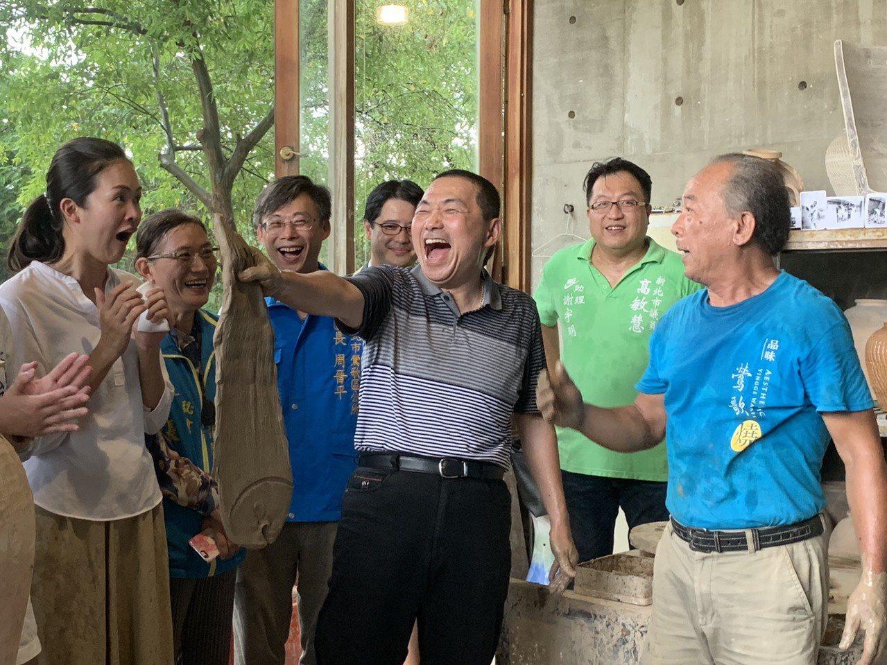 侯友宜今天到陶博館體驗捏陶,老師詹國祥(右一)當場捏出「一條魚」,要侯施法讓它長...