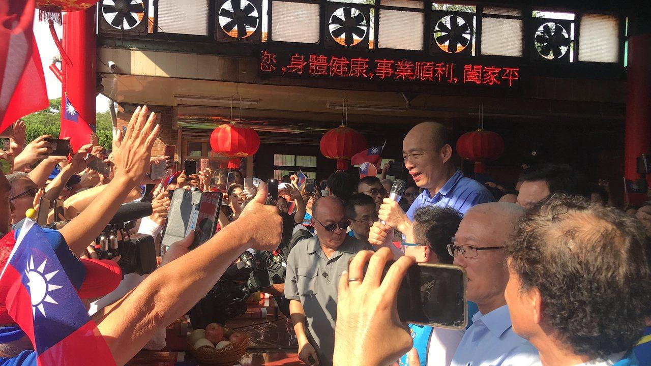 國民黨總統參選人韓國瑜站在桌子前致詞,與民眾距離不到兩步,現場的韓粉開心拿著手機...