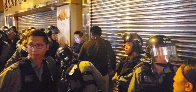 晚間七時開始,香港警員在德輔道西一帶截查黑衣人和可疑人士。(星島網)