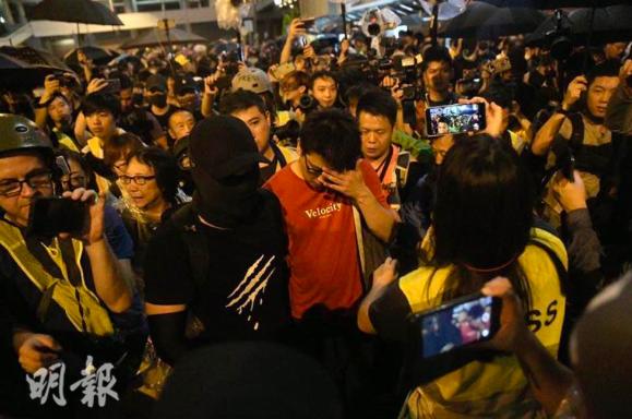 一名紅衣男子被示威者包圍,他強調自己不是公安。(明報網)