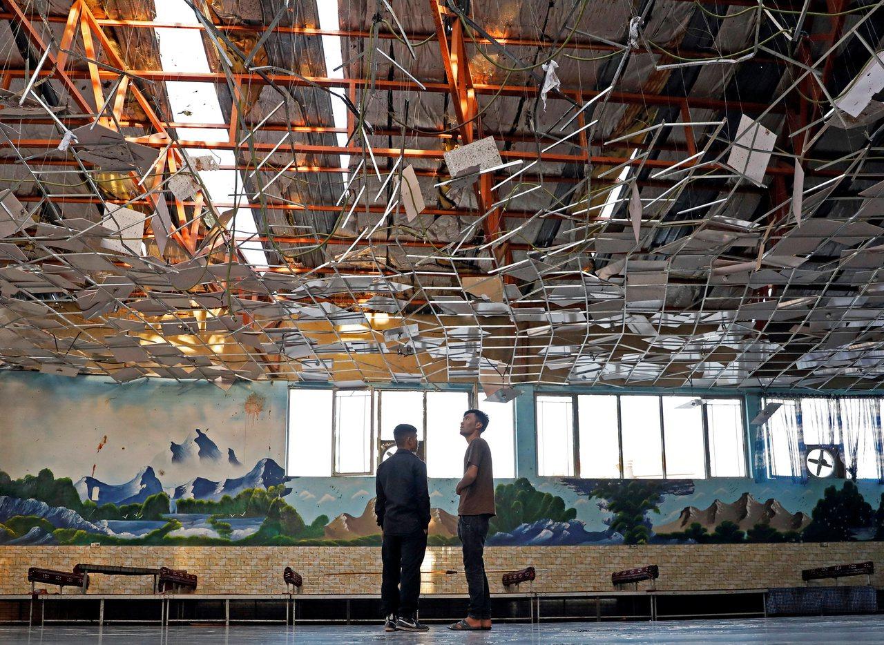 工作人員在18日檢查爆炸後的大禮堂內部。路透