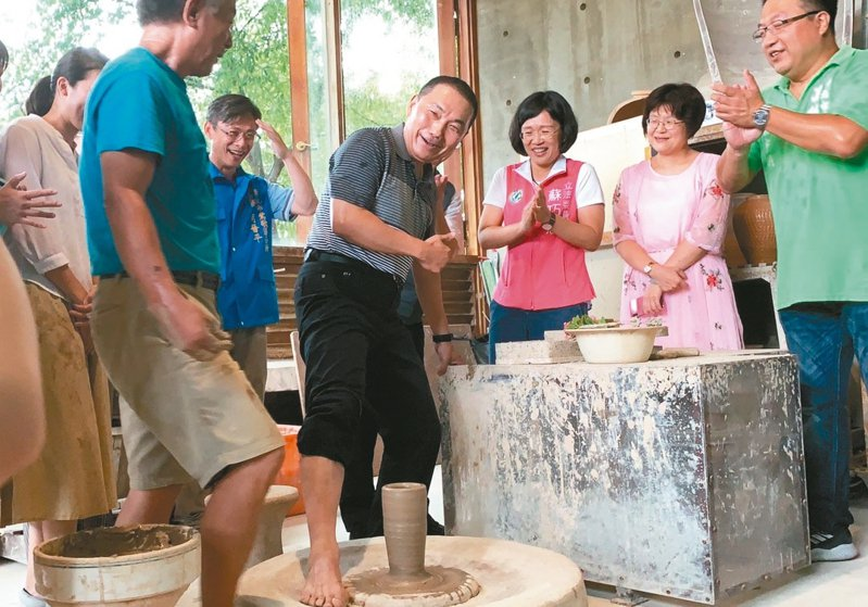 新北市長侯友宜(中)昨到陶博館向「台灣國腳」詹國祥學習「腳踢轆轤」絕技。 記者張曼蘋/攝影