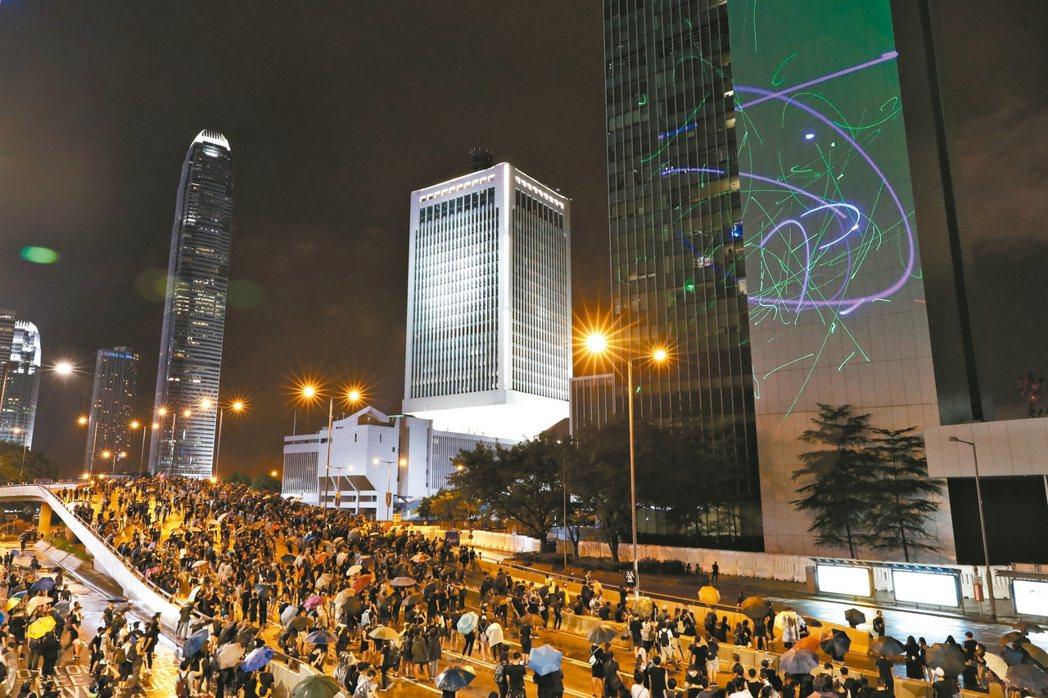 香港抗議民眾十八日晚間冒雨撐傘上街示威,用雷射筆照射特區政府總部外牆。 美聯社