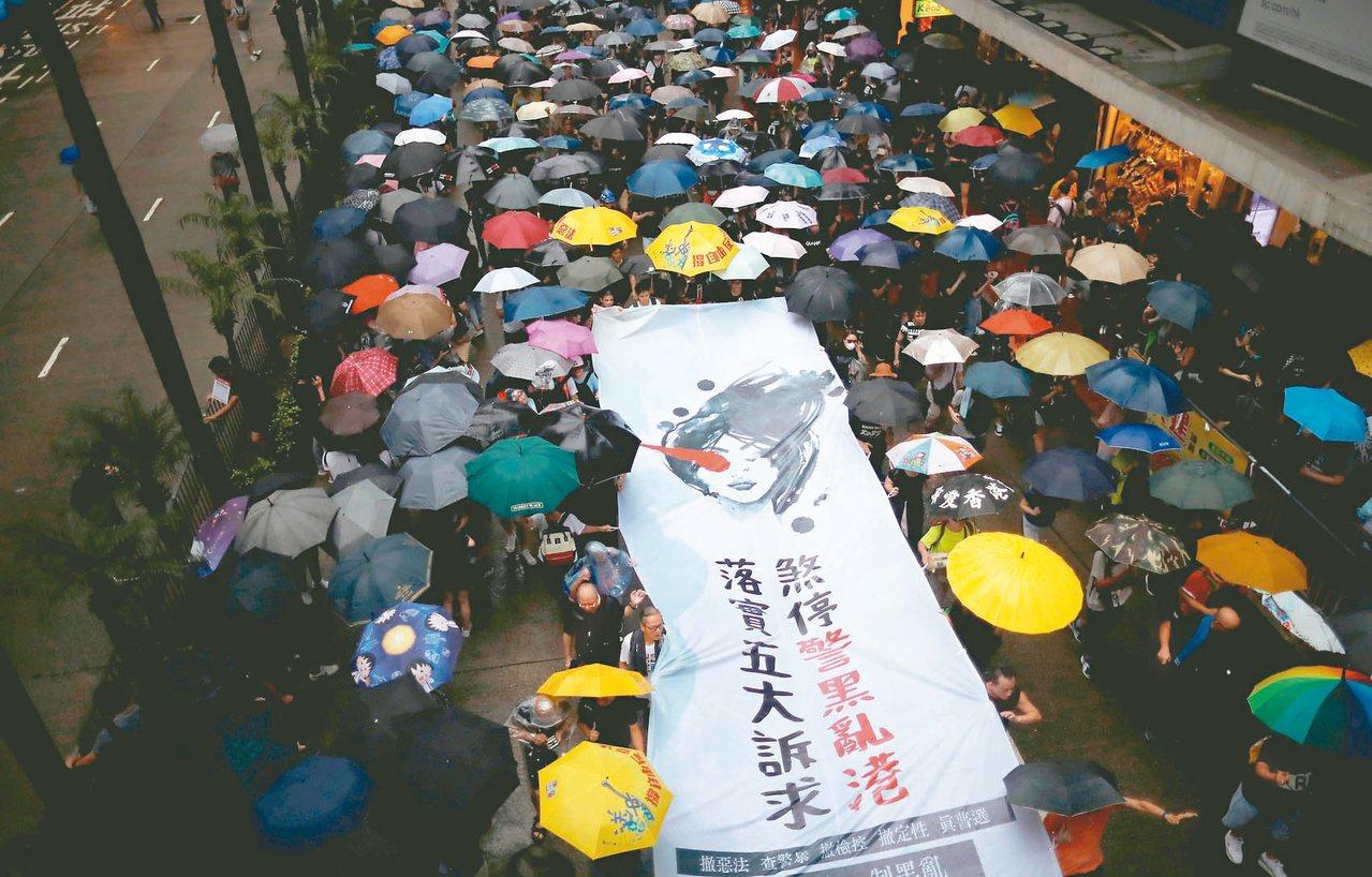 香港民眾十八日冒雨撐傘上街示威,要求實施「真普選」等民主改革。 (路透)