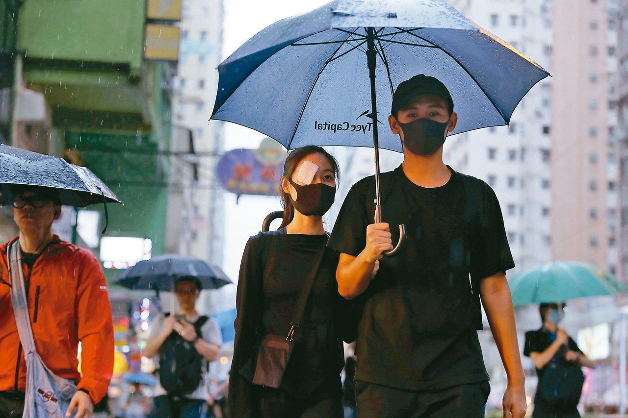 一名反送中示威者(中)十八日在香港遊行時,以紗布遮蓋右眼,以示支持疑遭警方射傷右...