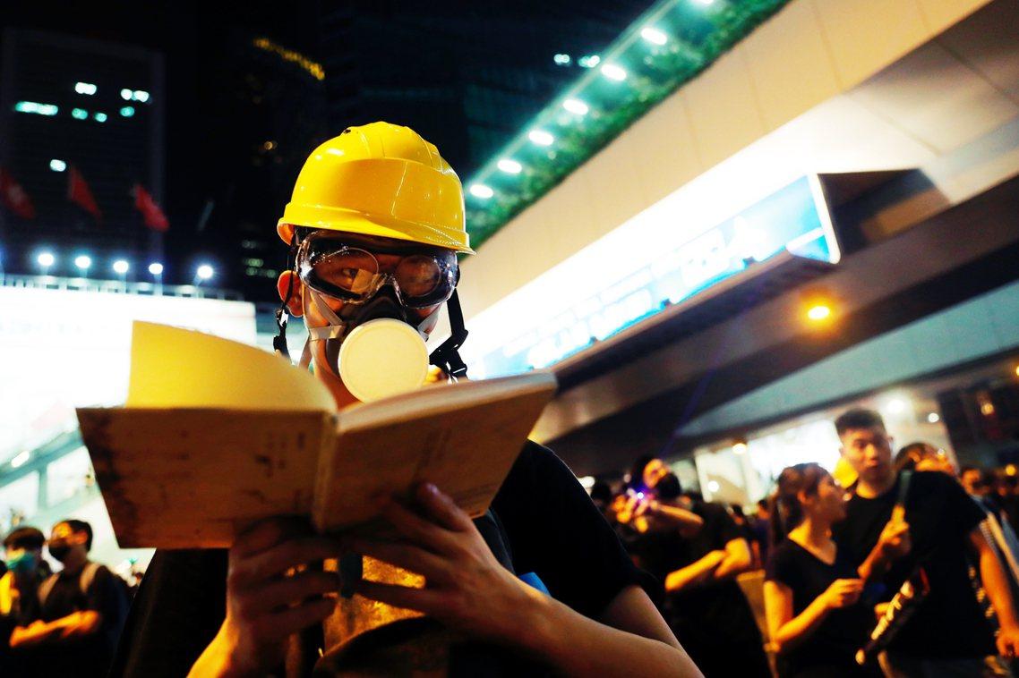 18日,沒有催淚彈的一天。帶著面具的示威者,正在集會場閱讀手裡的詩集。 圖/路透...