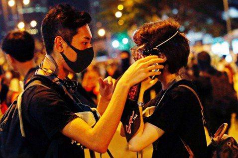 18日,沒有催淚彈的一天。一名示威者在幫忙同伴調整面具。 圖/路透社