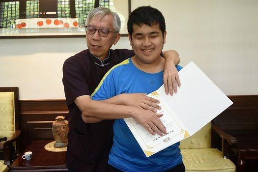 國父紀念館館長梁永斐與沈彥霖同學摸讀點字獎狀。  國父紀念館/提供