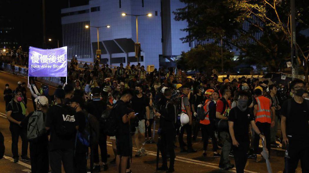 香港抗議人士昨天在駐香港特別行政區聯絡辦公室集結後,有人舉起「慢慢後退」的布幔,...