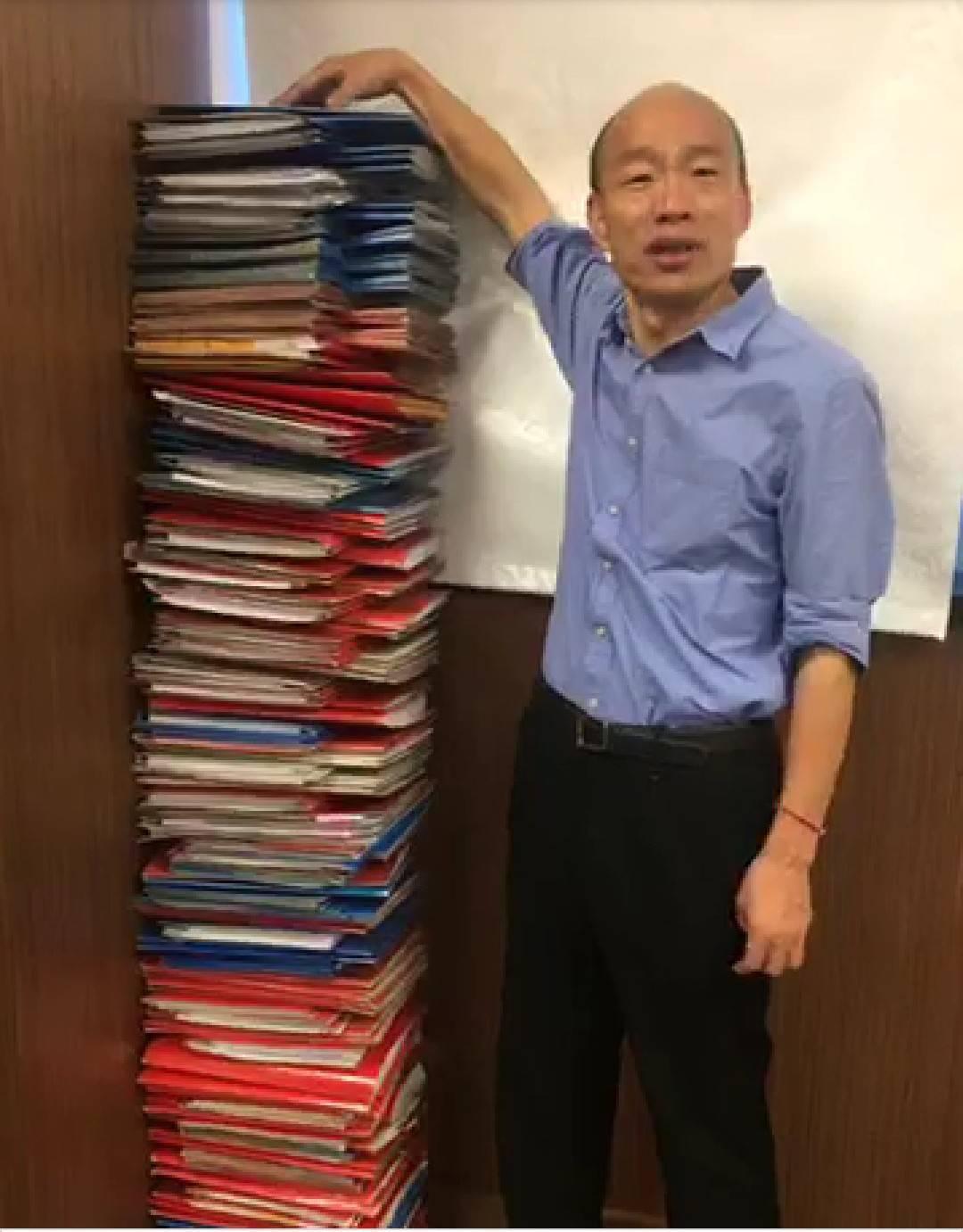 高雄市長韓國瑜昨在臉書直播,堆出跟他人一樣高的公文說要跟行政院長蘇貞昌「PK」,...