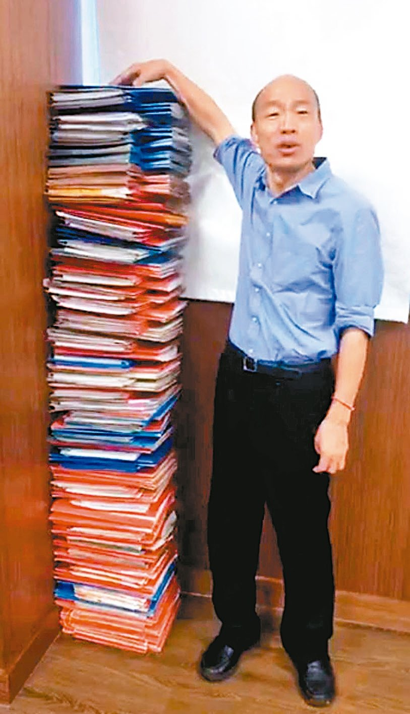 高雄市長韓國瑜(圖)昨開直播,堆出和他身高一樣高的公文跟行政院長蘇貞昌PK,強調...