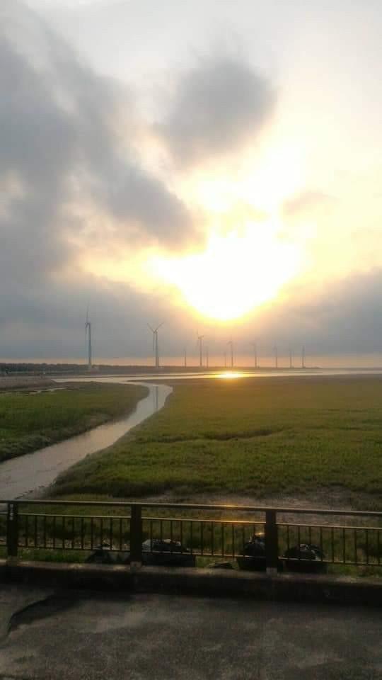 高美濕地夕陽美景有名,有人拍照時發現海堤欄杆旁有黑色大型垃圾袋,破壞美景。圖/取...