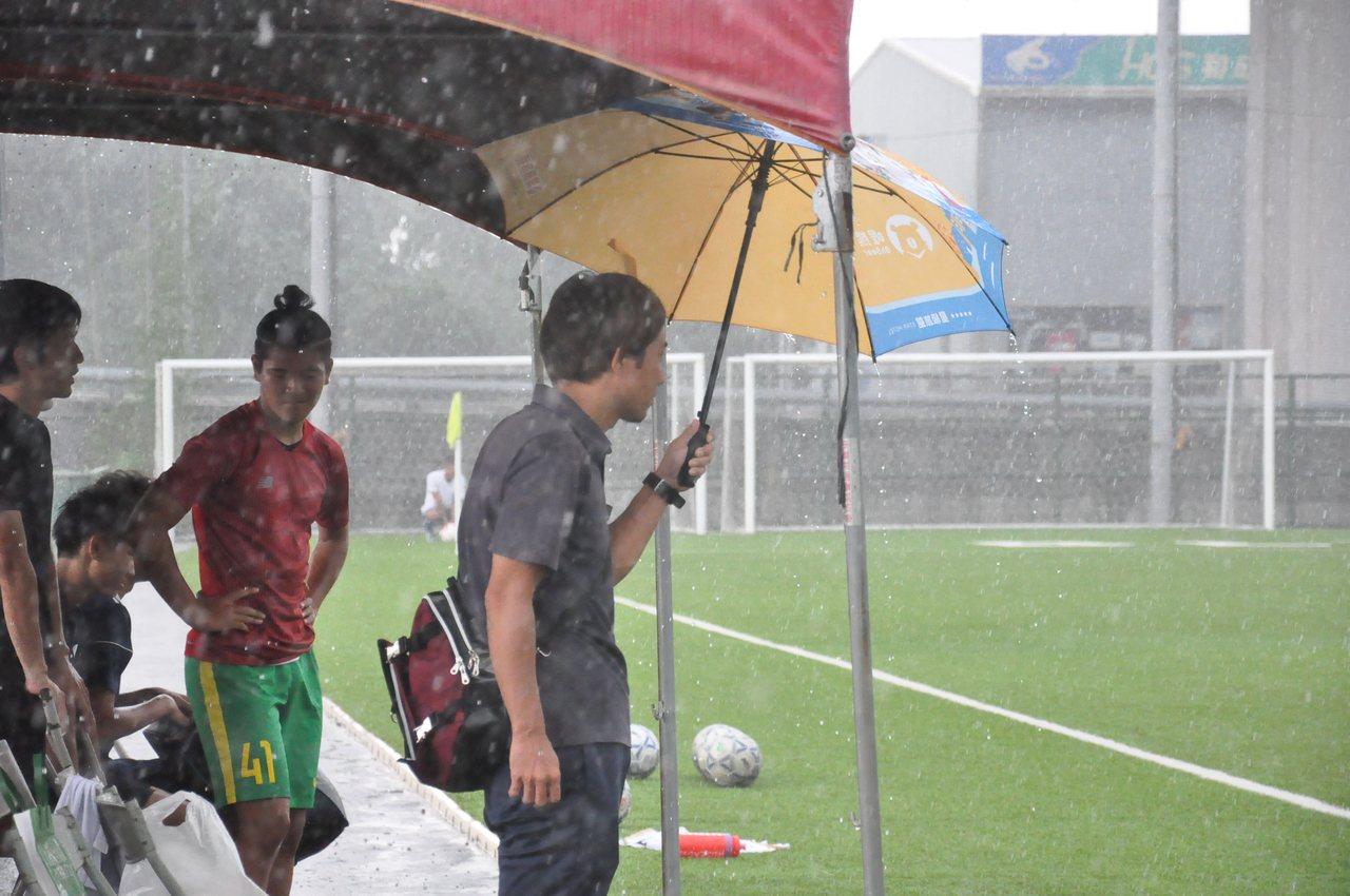台中下午下起傾盆大雨,球員帳篷也無法阻擋雨勢,球隊人員直接撐傘擋雨。記者曾思儒/...