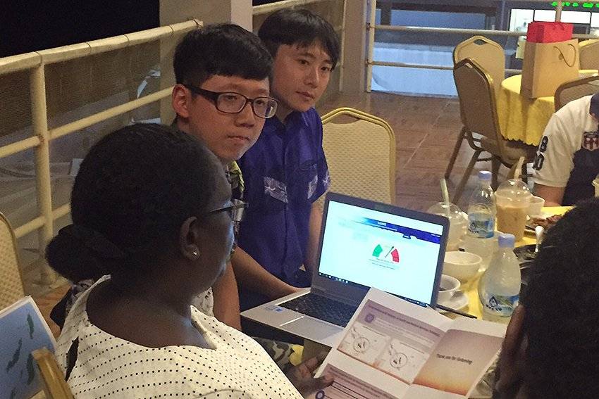 中原大學環工系學生林昱翰(左二)向索國官員解說類登革熱預警系統的建置構想。 中原...