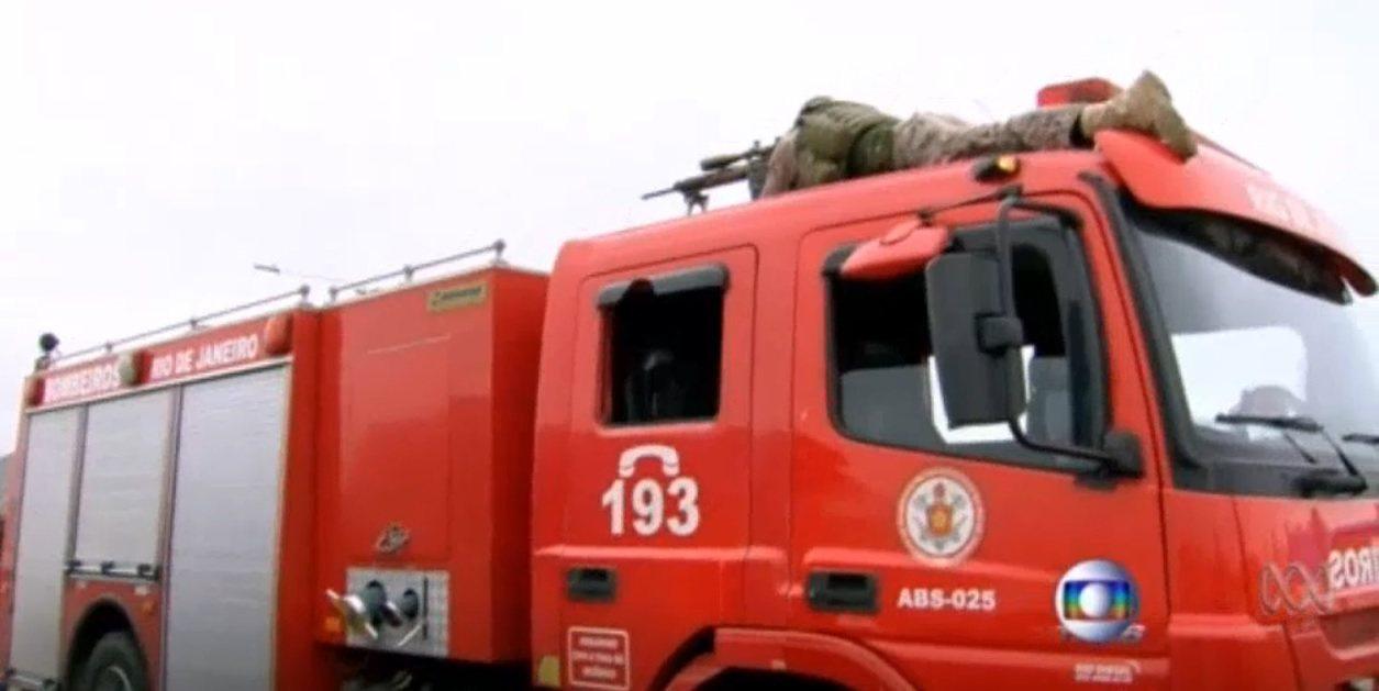 狙擊手趴在消防車車頂,等候開槍時機。取自澳洲新聞網影片