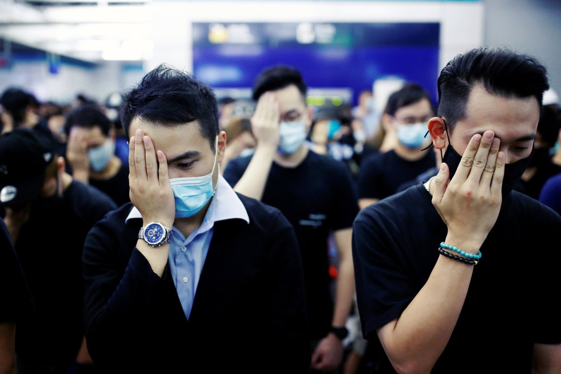 集會期間,示威者以靜坐或站立默哀的方式,為反送中傷者致意,同時也以手遮住右眼,響...