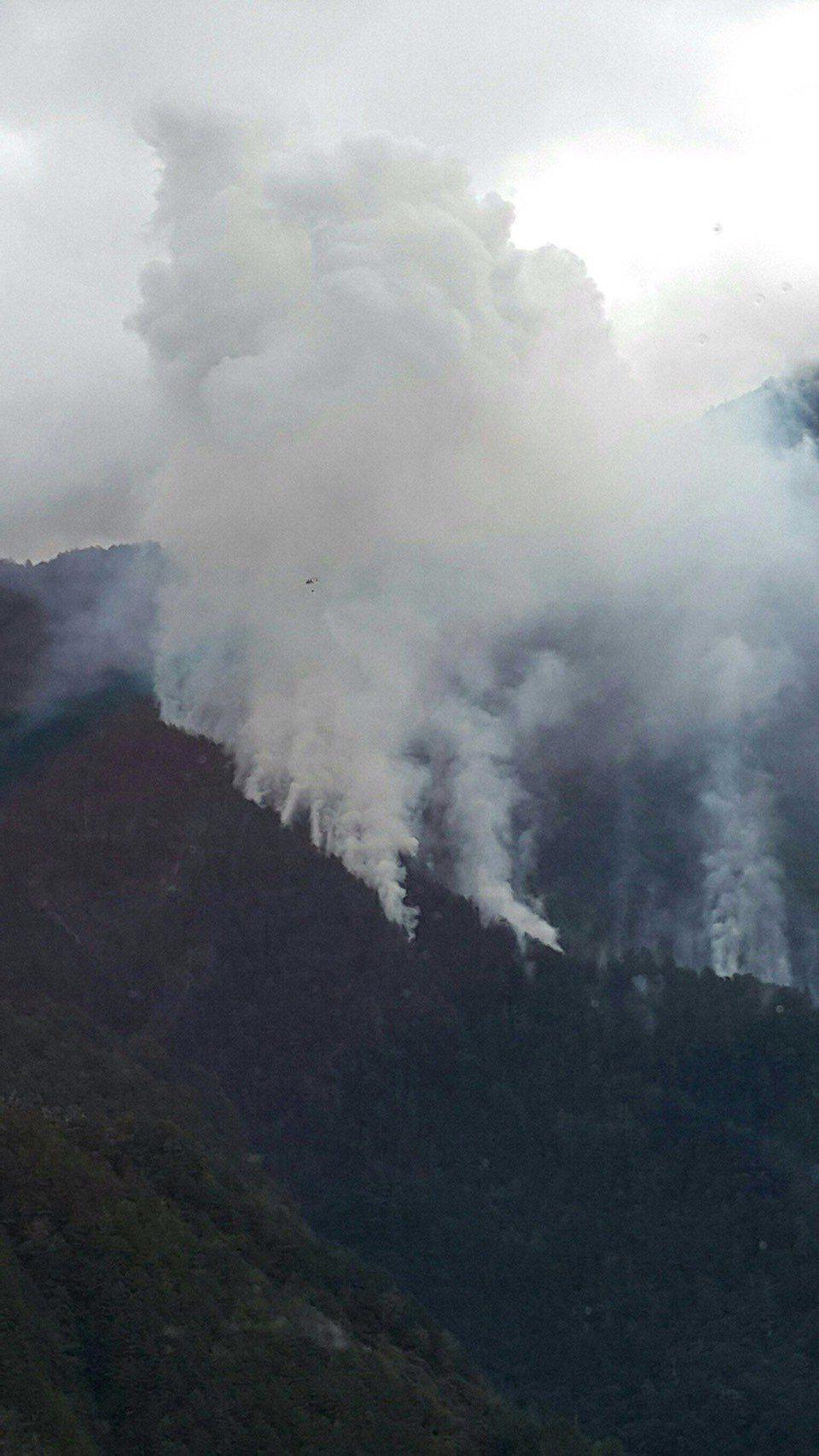 空勤總隊直升機到高山協助滅火,在大火濃煙中,可看到直升機只剩一個黑點,任務危險。...