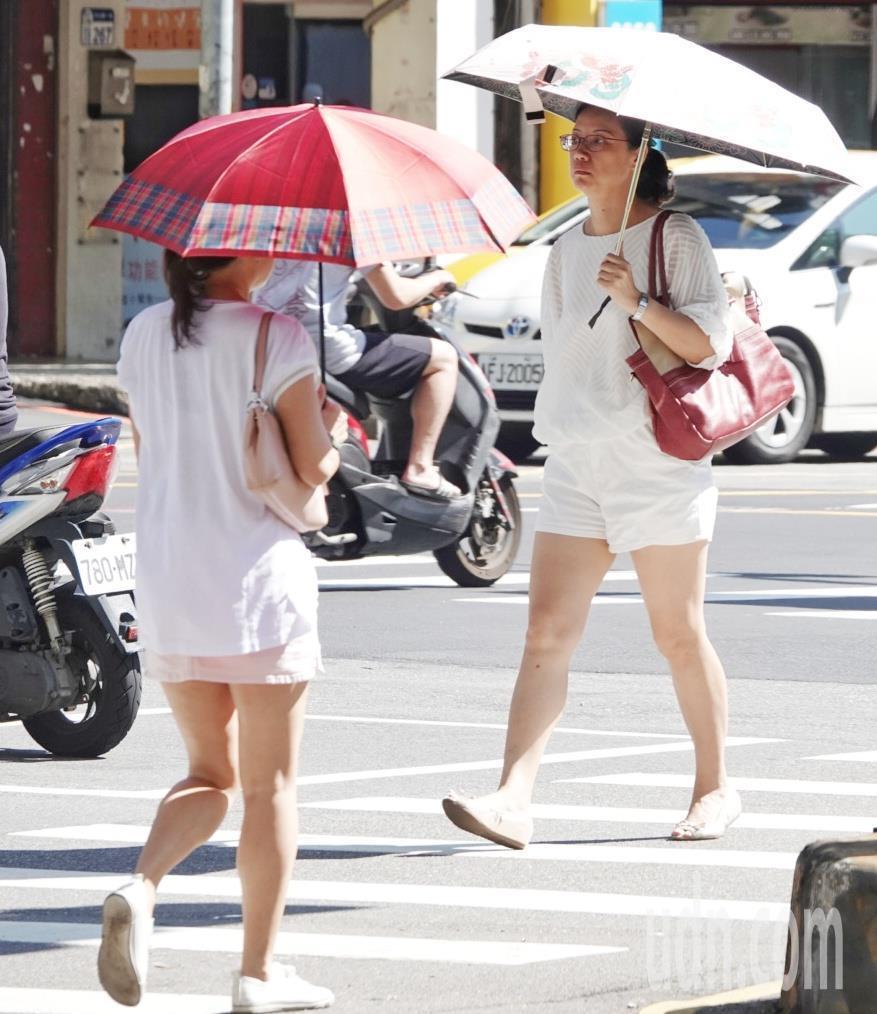 輕颱白鹿將至,台北上午氣候炎熱,民眾撐傘出門抵抗豔陽照射。記者陳正興/攝影