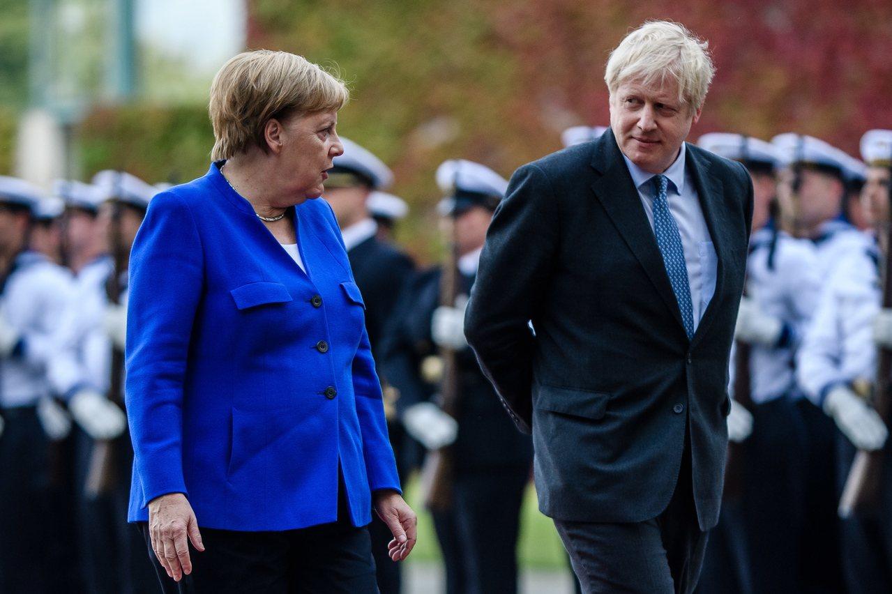 英國首相強生(右)上台後首次出訪,與德國總理梅克爾(左)會談。歐新社