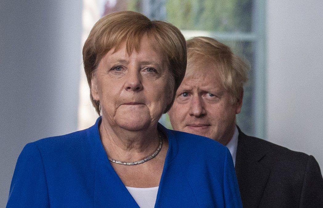 德國總理梅克爾(左)21日在首都柏林歡迎來訪的英國首相強生。(法新社)