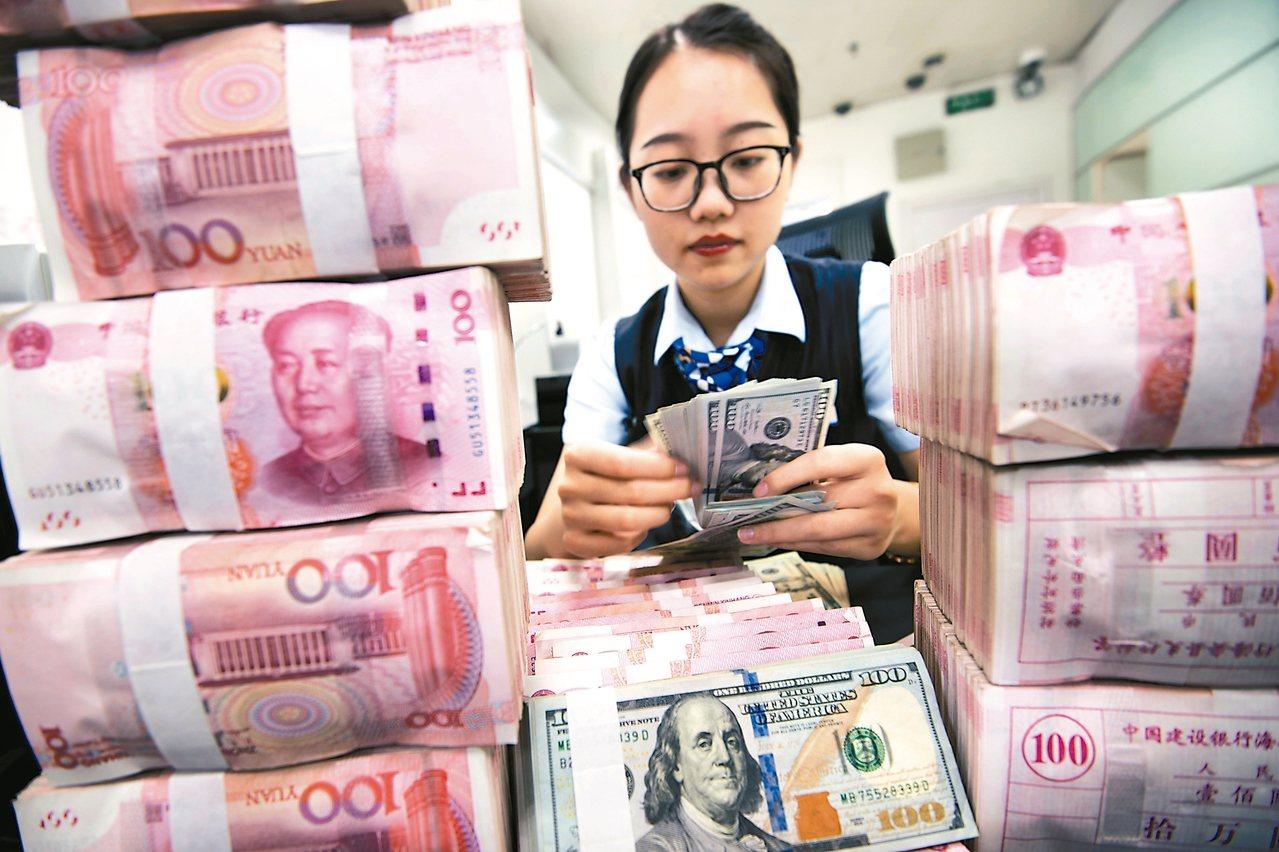 美聯社說,美中貨幣戰開打的可能性愈來愈高。圖為大陸江蘇省銀行人員數算人民幣鈔票。...