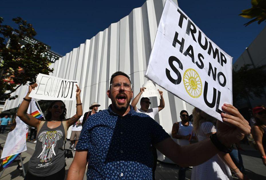 示威者9日在加州西好萊塢市抗議羅斯為川普募款,揚言抵制羅斯旗下豪華健身俱樂部。圖右標語寫著「川普沒有『心靈』」。 (法新社)