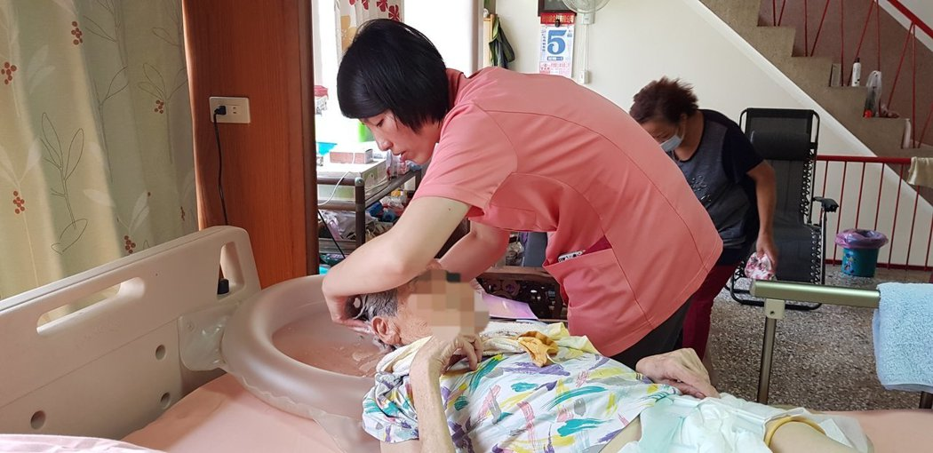 成大醫院安寧居家護理師(中)到癌症末期患者家中協助洗頭,讓病患舒適。記者修瑞瑩/攝影