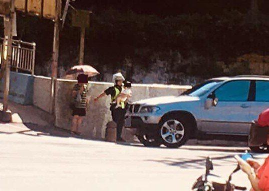 有網友在「基隆人大小事」臉書社群貼文,一名女警處理車禍還要幫忙抱小孩。圖/取自基...