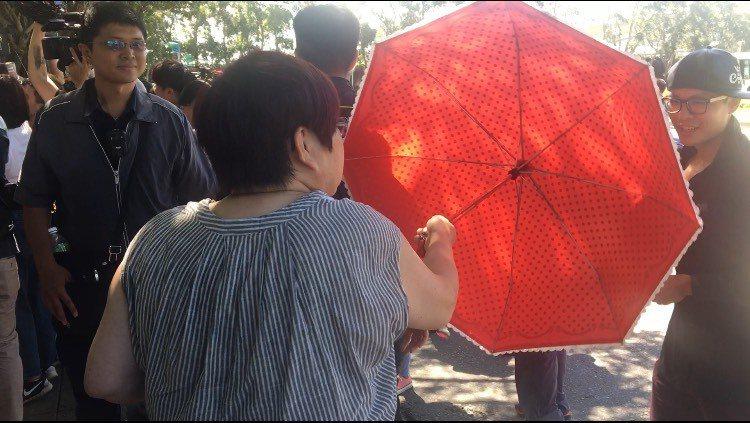 女性韓粉利用雨傘阻擋攝影機拍攝,並批郭台銘是出來騙票。記者郭頤/攝影